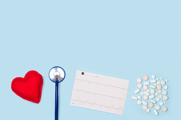 Stetoskop, elektrokardiogram i tabletki medyczne na jasnoniebieskim tle