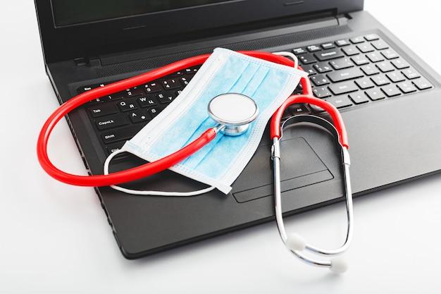 Stetoskop i chirurgicznie maska ochronna na laptopie. pojęcie opieki zdrowotnej medycyny. miejsce pracy lekarzy do czatu wideo, konsultacji online, wizyty u lekarza. zapobieganie koronawirusowi covid-19 covid19