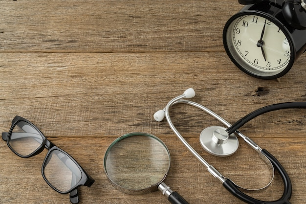 Stetoskop i czarny budzik vintage z miejscem na kopię na drewnianym tle