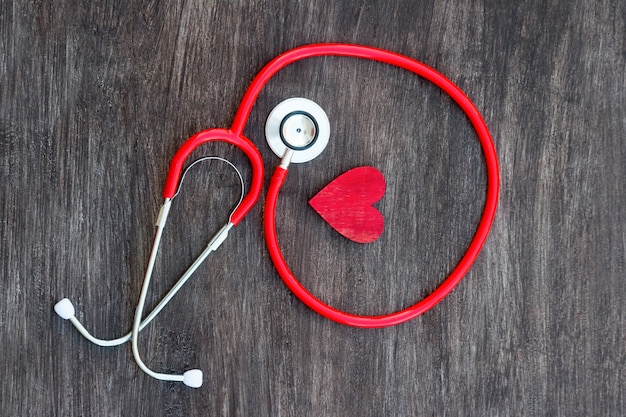 Stetoskop i czerwone serce na drewnianym