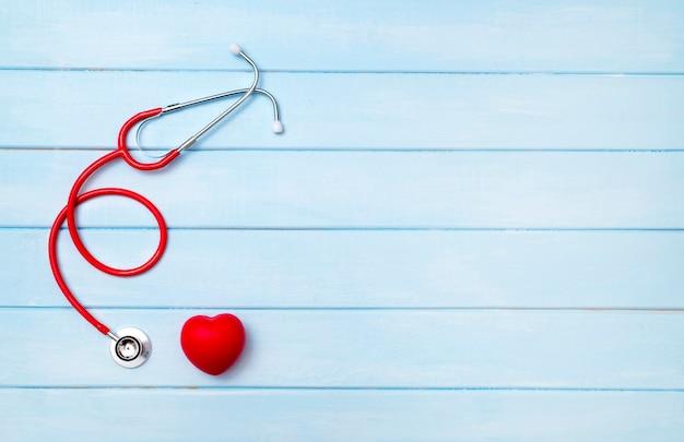 Stetoskop i czerwone serce na niebieskim drewnianym