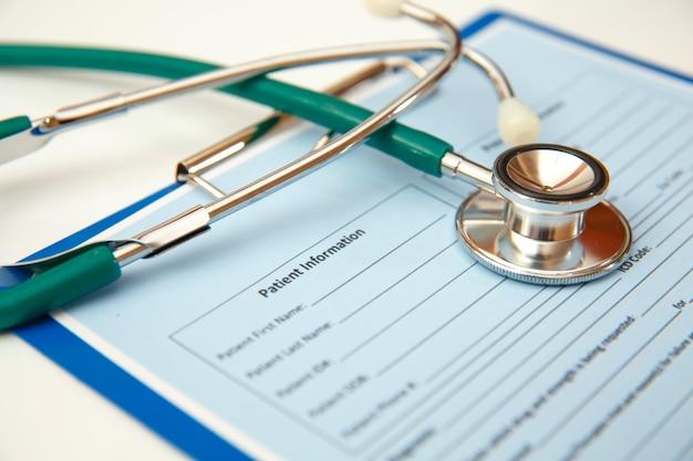 Stetoskop i formularz wizyty pacjenta na białym stole