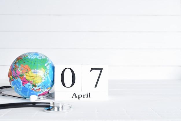 Stetoskop i kula ziemska z kwietnia 7 teksta drewnianym blokowym kalendarzem na białym drewnianym tle.