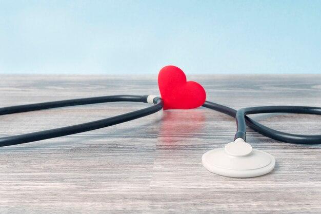 Stetoskop i małe serce na drewnianym stole.