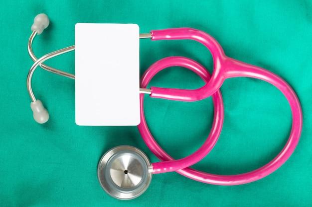 Stetoskop i pusta biała wizytówka na zielonej koszuli lekarza