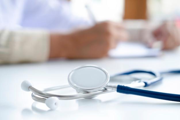 Stetoskop i schowek na miejsce pracy lekarzy w tle, lekarz udzielający zdalnej konsultacji medycznej przez internet.