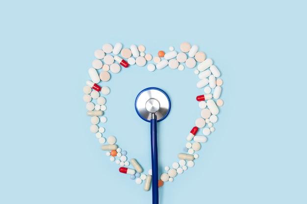 Stetoskop i serce wykonane z tabletek medycznych na jasnoniebieskim tle