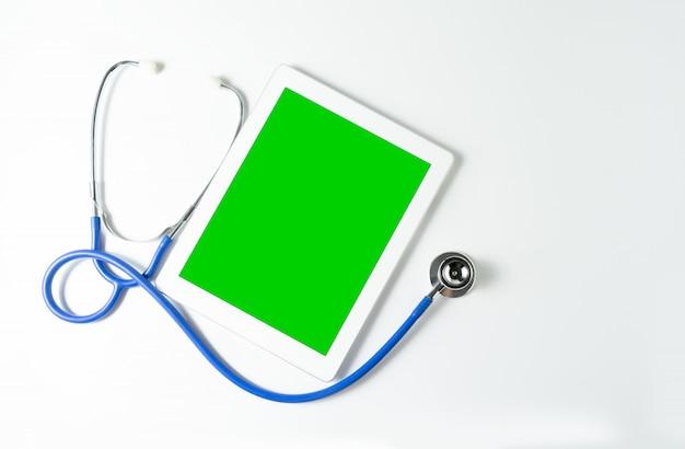 Stetoskop i tablet na zielony ekran, białe tło, kopiować miejsca na tekst