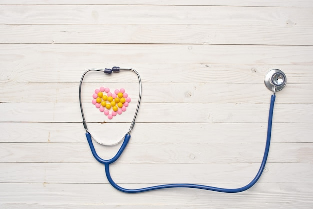 Stetoskop lekarstwa szpitalne pigułki drewniane tło