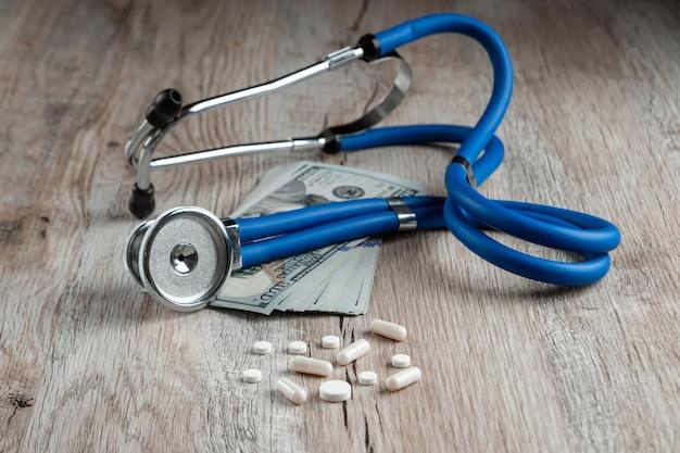 Stetoskop leży na pakiecie pieniędzy i tabletek na lekkim drewnianym stole