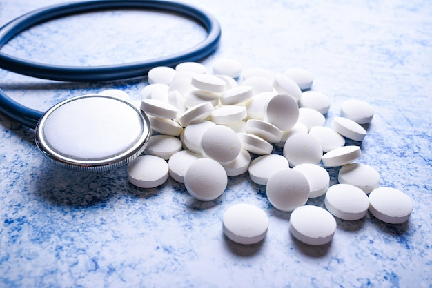 Stetoskop medyczny i wiele białych tabletek niebieska powierzchnia. koncepcja kardiologii