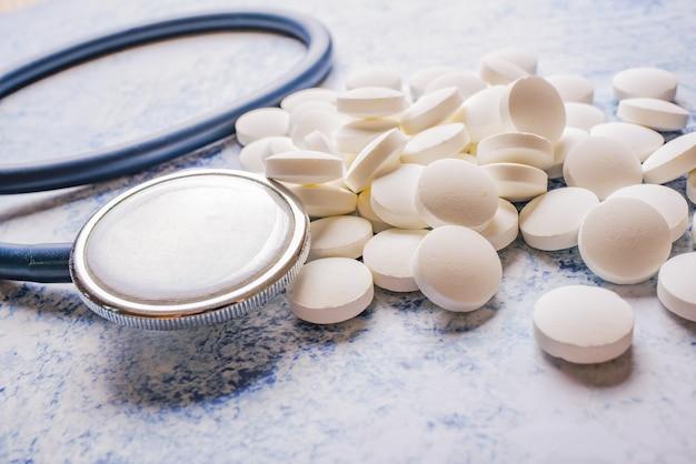 Stetoskop medyczny i wiele białych tabletek niebieskich