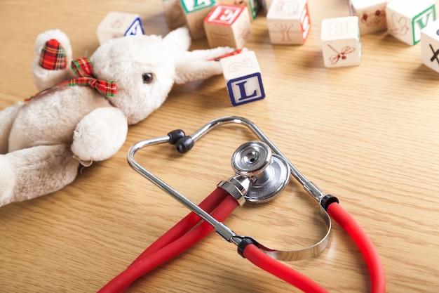 Stetoskop medyczny i zabawki na drewnianym tle