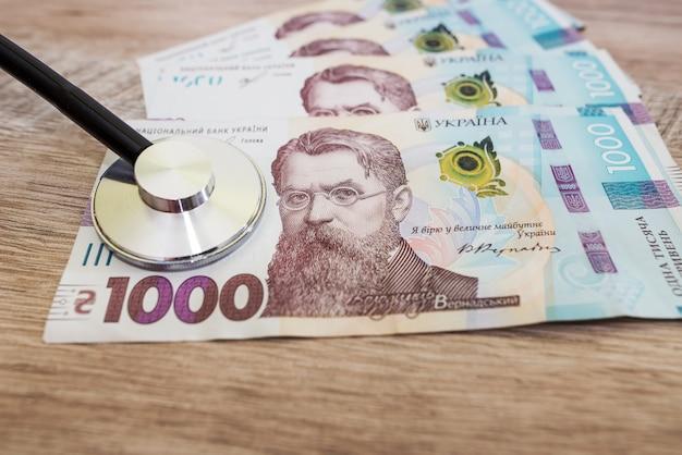 Stetoskop na banknotach 1000 hrywien, koncepcja płatności opieki zdrowotnej.