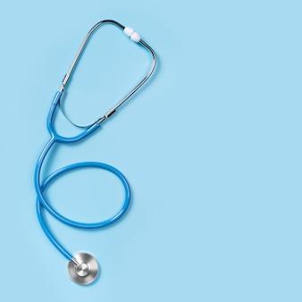 Stetoskop na białym tle na niebieskim tle, widok z góry. narzędzia medyczne. stetoskop jest ważnym narzędziem diagnostycznym dla lekarza.