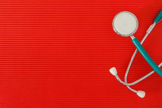 Stetoskop na czerwonym tle widok z góry z wolnej przestrzeni