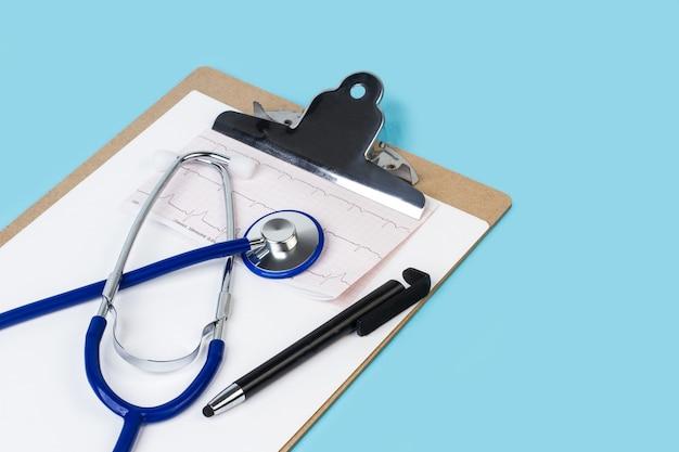Stetoskop na elektrokardiogramie i w schowku na jasnoniebieskim tle