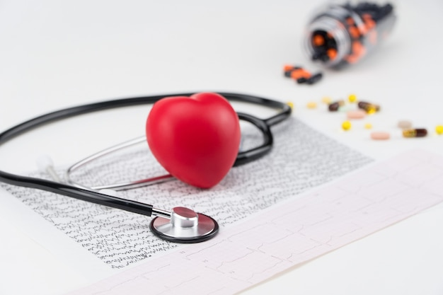 Stetoskop na kardiogramie i zabawkowym sercu. pojęcie opieki zdrowotnej. kardiologia - pielęgnacja serca