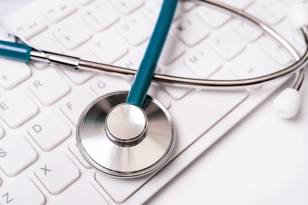 Stetoskop na klawiaturze komputera. lekarz pisze przypadek medyczny koncepcja leczenia długoterminowego z bliska kopia przestrzeń makro