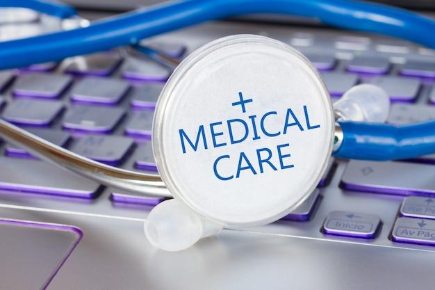 Stetoskop na klawiaturze notebooka ze słowami opieka medyczna - koncepcja nowoczesnej medycyny
