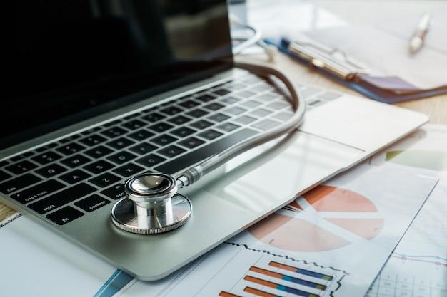 Stetoskop na komputerze z wynikami testu w wykresie raportu konsultacji lekarza pokoju