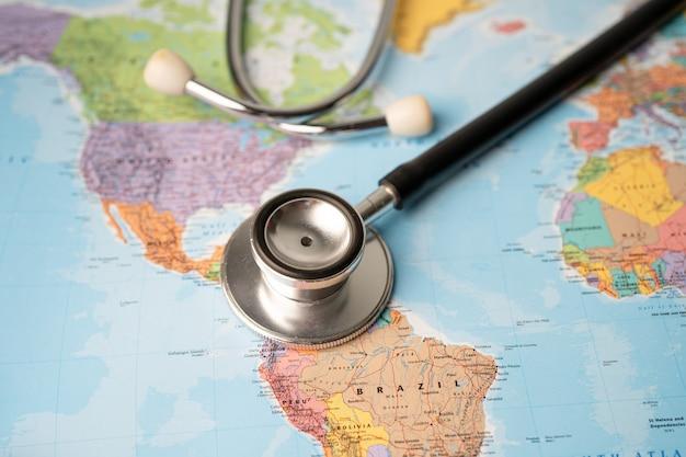 Stetoskop na mapie świata w usa, ameryce i brazylii.