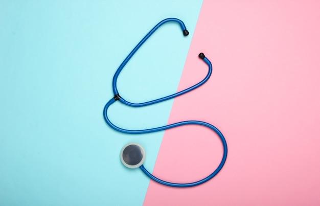 Stetoskop na niebiesko-różowym pastelowym tle. widok z góry