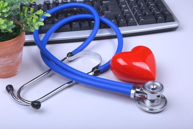 Stetoskop na nowoczesnym laptopie. czerwone serce na białym stole z miejscem na tekst. pojęcie opieki zdrowotnej.