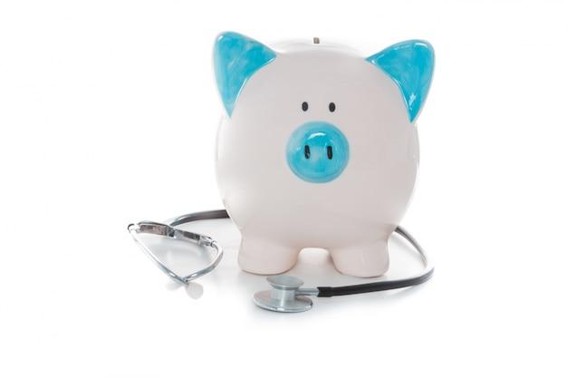 Stetoskop owinięty wokół niebieski i biały piggy bank