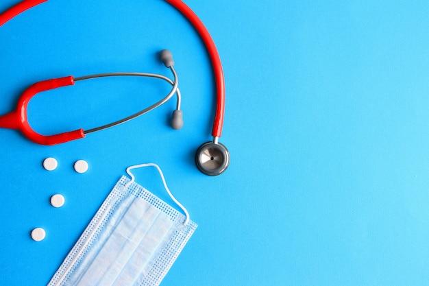 Stetoskop, pigułki i maska medyczna na niebieskim tle koncepcji medycyny, zdrowia, choroby