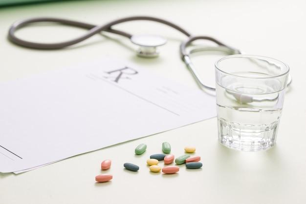 Stetoskop, pigułki i szklankę wody na jasnozielonym tle. koncepcja medycyny