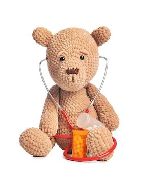 Stetoskop, pigułki i zabawka dla dziecka na białym