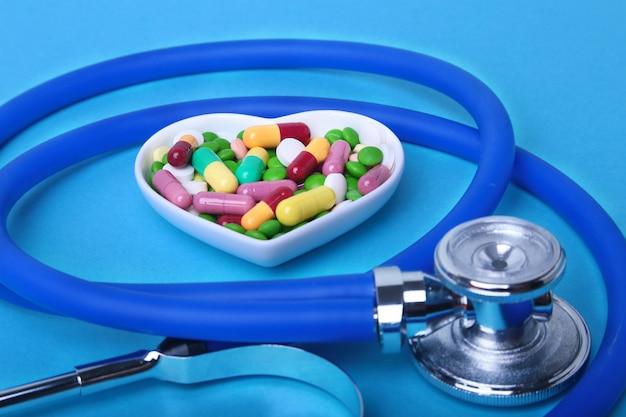 Stetoskop, rx na receptę i kolorowe pigułki asortymentowe i kapsułki na talerzu.