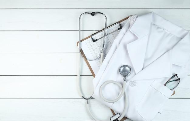 Stetoskop, schowka i lekarza na jednolitym drewnianym biurku