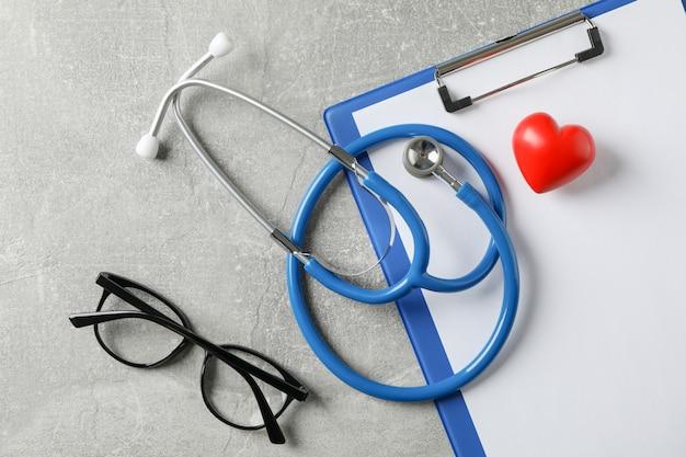 Stetoskop, serce, pastylka i szkła na szarym tle, zamykają up