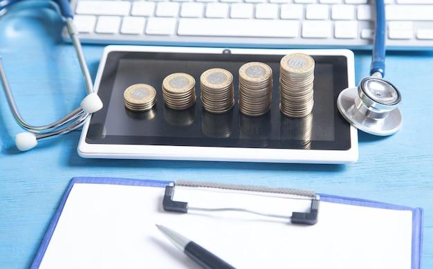 Stetoskop, tablet, klawiatura komputerowa i monety na niebieskim tle.