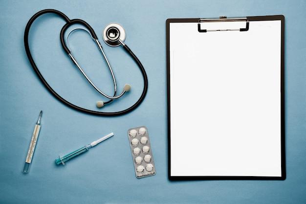 Stetoskop, tabletki w blistrze, strzykawka, termometr i teczka na notatki leżą na niebieskim tle. jest miejsce na napis