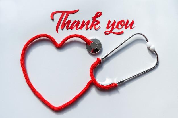 Stetoskop tworząc serce z jego sznur na białym tle. grafika papierowa z napisem dziękuję. koncepcja opieki zdrowotnej. miejsce na tekst. nieostrość. widok z góry. leżał na płasko.