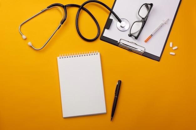 Stetoskop w biurku lekarza z notatnikiem i pigułkami. widok z góry z miejscem na twój tekst.