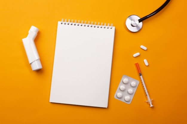 Stetoskop w biurku lekarza z notatnikiem, inhalatorem i pigułkami. widok z góry z miejscem na twój tekst.