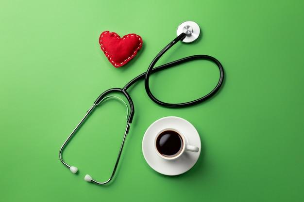 Stetoskop w biurku lekarzy z filiżanką kawy i serca