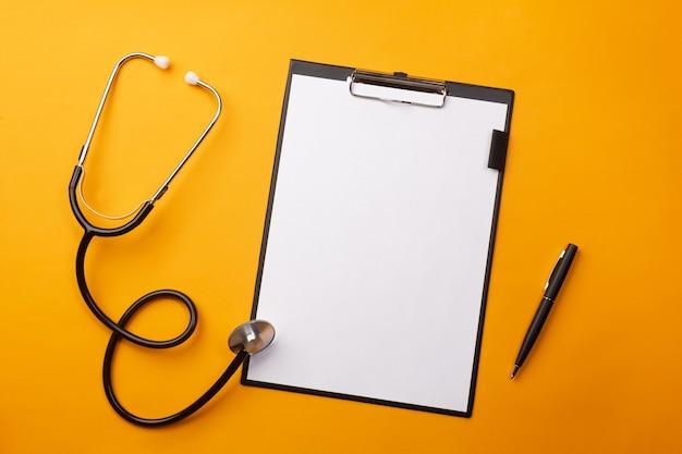 Stetoskop w biurku lekarzy z tabletu, długopis i pigułki