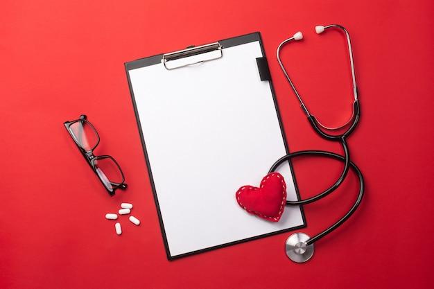 Stetoskop w biurku lekarzy z tabletu, serca i pigułki, widok z góry