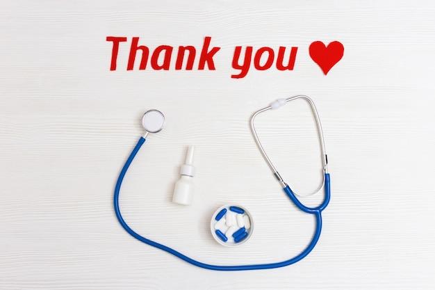"""Stetoskop w kolorze niebieskim, pigułki, czerwone serce i tekst """"dziękuję"""" na białym tle"""
