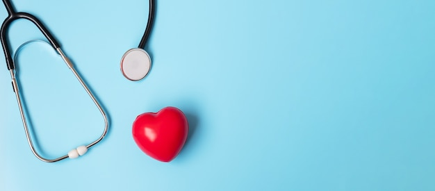 Stetoskop w kształcie czerwonego serca na niebieskim tle