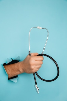 Stetoskop w męskiej dłoni w otworze