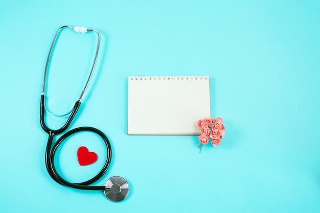 Stetoskop z czerwonym sercem, małymi kwiatami i notatnikiem