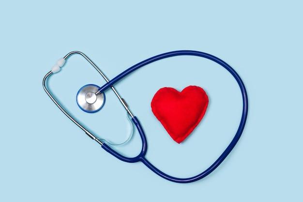 Stetoskop z czerwonym sercem na jasnoniebieskim tle w widoku z góry
