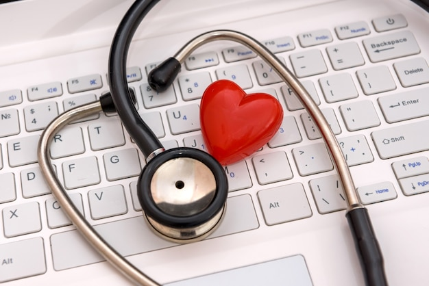 Stetoskop z czerwonym sercem na klawiaturze laptopa