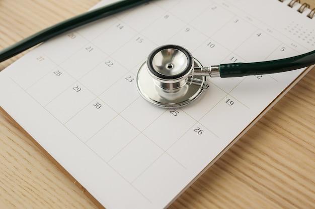 Stetoskop z datą strony kalendarza na tle stołu z drewna koncepcja medyczna powołania lekarza